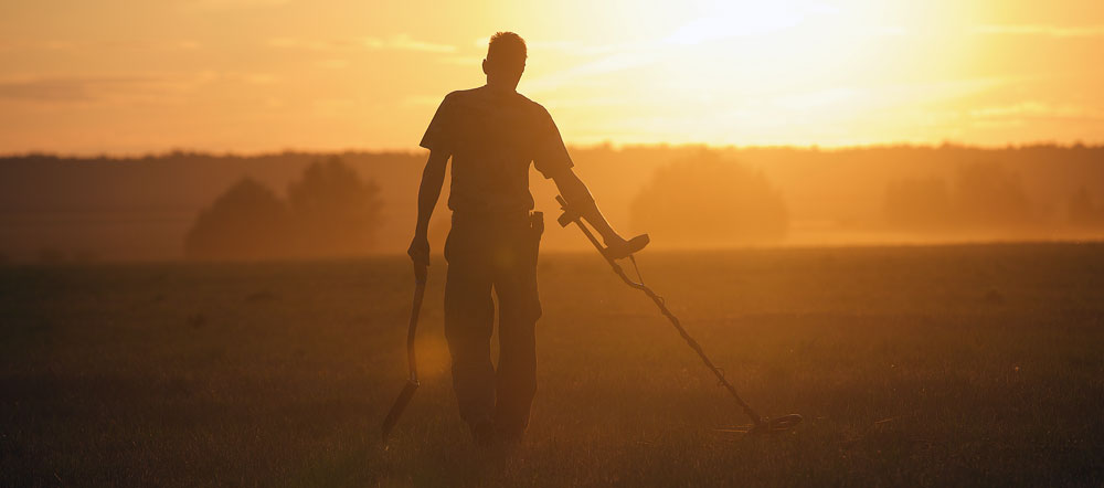 A man metal detecting at sunset