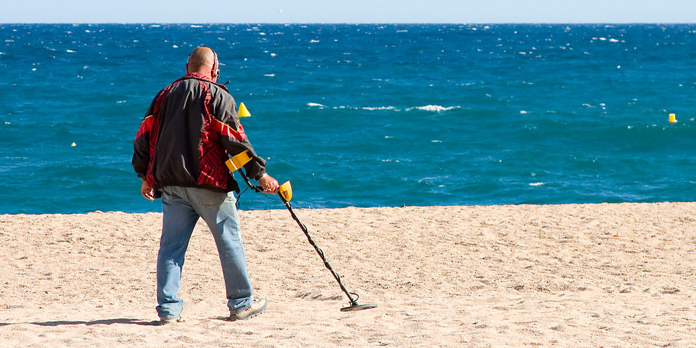 Man metal detecting at beach